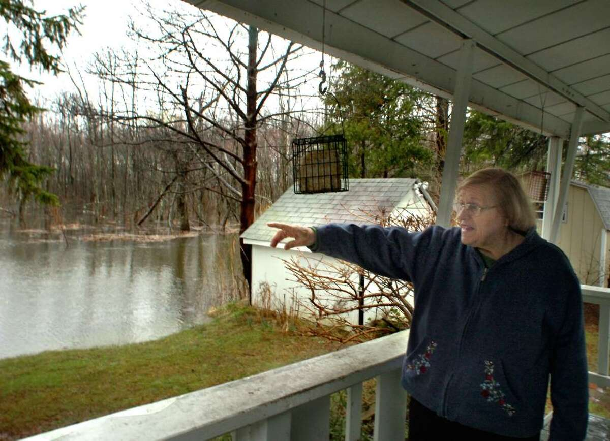 June Wildberger, 79, points toward Lake Kenosia, the source of the floodwaters rising around her home in Jensens Lakeview mobile home park in Danbury on Tuesday, 2010.