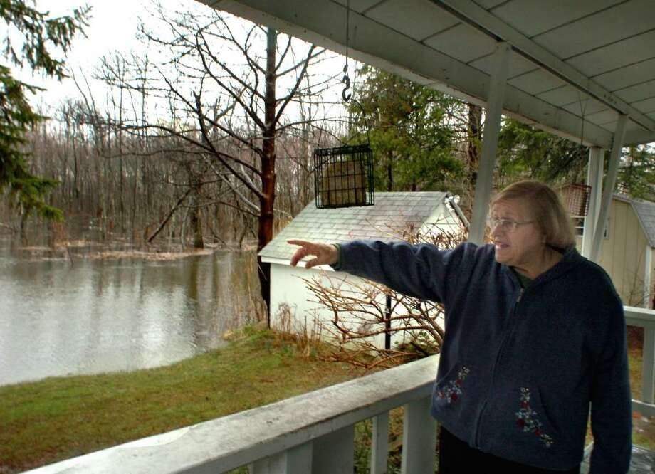 June Wildberger, 79, points toward Lake Kenosia, the source of the floodwaters rising around her home in Jensens Lakeview mobile home park in Danbury on Tuesday, 2010. Photo: Michael Duffy / The News-Times