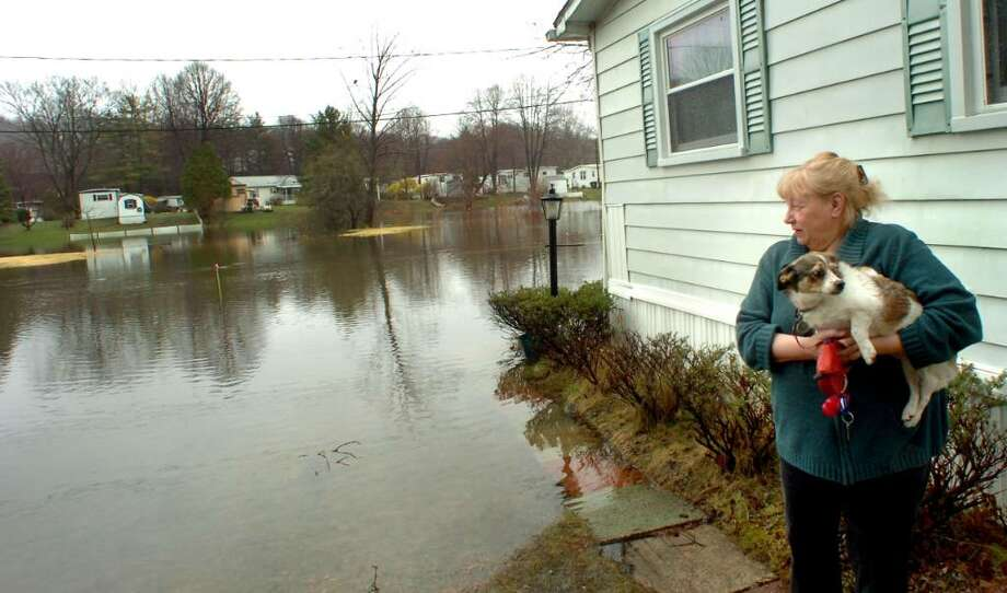 Fran Hendrickson, 65, holds Sophie and watches the water rise around her home in Jensens Lakeview mobile home park in Danbury on Tuesday, 2010. Photo: Michael Duffy / The News-Times