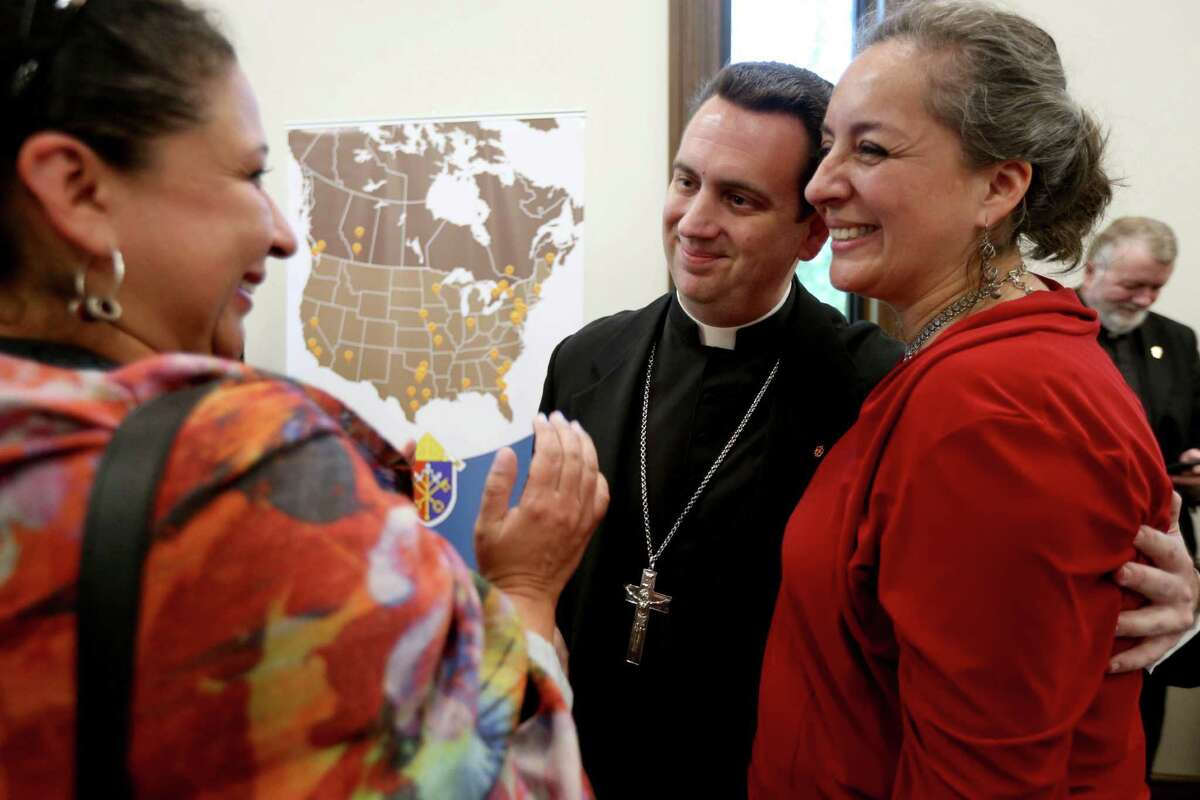 The Rev. Monsignor Steven J. Lopes, shown with Catholic Church members Juliana Missas, left, and Catalina Brand, both of Houston, after Rev. Lopes was introduced to be the first bishop of the Personal Ordinariate of the Chair of St. Peter, named by Pope Francis, at the Ordinariate's Chancery Tuesday, Nov. 24, 2015, in Houston, Texas. Msgr. Jeffrey N. Steenson, the leader of the Ordinariate since 2012, introduced Bishop-elect Lopes.