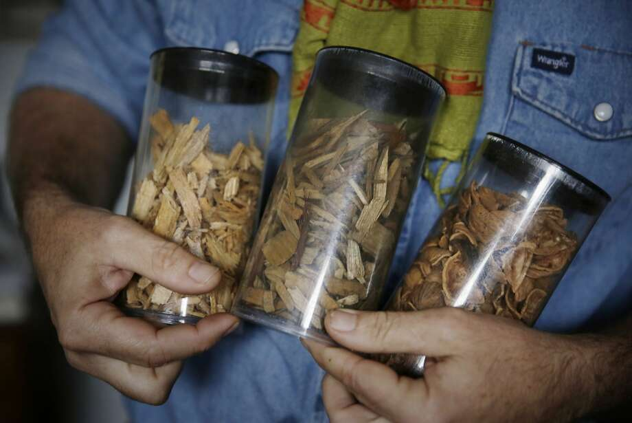 A worker holds samples of woody biomass used in All Power products. Photo: Lea Suzuki, The Chronicle