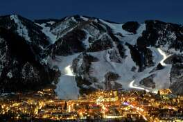 Aspen's ski slopes are illuminated with the help of a full moon, while night life keeps the city streets aglow.