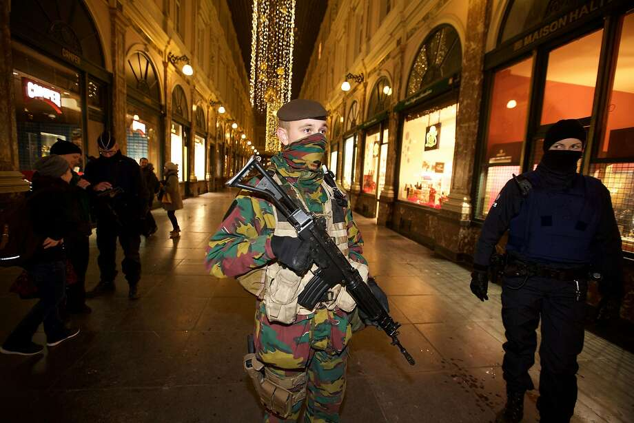 """Soldiers and police patrol in Brussels. The Belgian capital has remained on high alert since the weekend for fear of a """"serious and imminent threat,"""" with schools, shops and subways shut. Photo: Nicolas Maeterlinck, AFP / Getty Images"""
