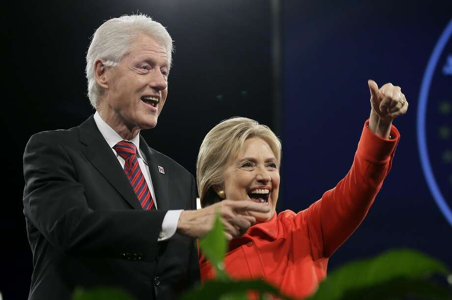 Former President Bill Clinton and his wife,Hillary Rodham Clinton, wave to supporters in Des Moines, Iowa. Photo: Charlie Neibergall, Associated Press