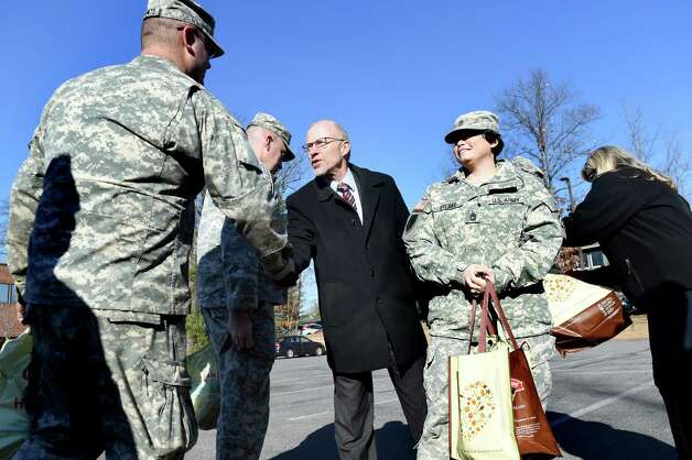 Dennis Martin of Hannaford, center, thanks National Guard members, SPC Dan Tagliento, left, and SFC Stephanie Fiebke for their service during the seventh annual Turkeys for Veterans on Tuesday, Nov. 24, 2015, at Tully Rinckey in Colonie, N.Y. Tully Rinckey and Hannaford Supermarkets handed out 200 turkeys to active duty and retired military personnel for their Thanksgiving Day dinners. (Cindy Schultz / Times Union) Photo: Cindy Schultz / 10034303A