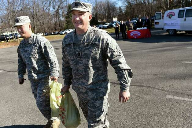 Army recruiting captains Eric Zachariasen, left, and Nathan LaSorba pick up their free turkeys during the seventh annual Turkeys for Veterans on Tuesday, Nov. 24, 2015, at Tully Rinckey in Colonie, N.Y. Tully Rinckey and Hannaford Supermarkets handed out 200 turkeys to active duty and retired military personnel for their Thanksgiving Day dinners. (Cindy Schultz / Times Union) Photo: Cindy Schultz / 10034303A