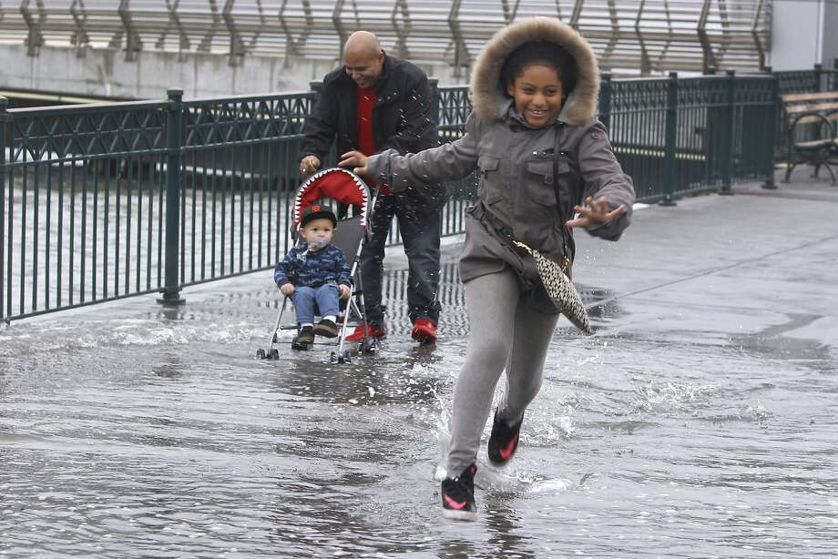 Araya Villareal dashes through water spilling onto the sidewalk with her father Isaac pushing his nephew Jamison McCall in a stroller at Pier 14 along the Embarcadero during high tide in San Francisco, Calif. on Tuesday, Nov. 24, 2015. King tide conditions are causing higher than usual water levels. Photo: Paul Chinn, The Chronicle