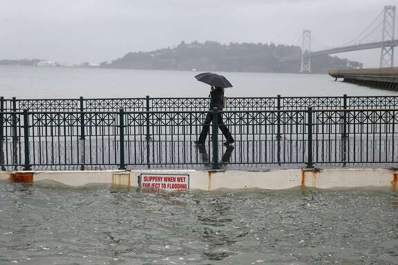 Luna Taylor walks off of Pier 14 during the peak of the high tide along the Embarcadero in San Francisco, Calif. on Tuesday, Nov. 24, 2015. King tide conditions are causing higher than usual water levels.