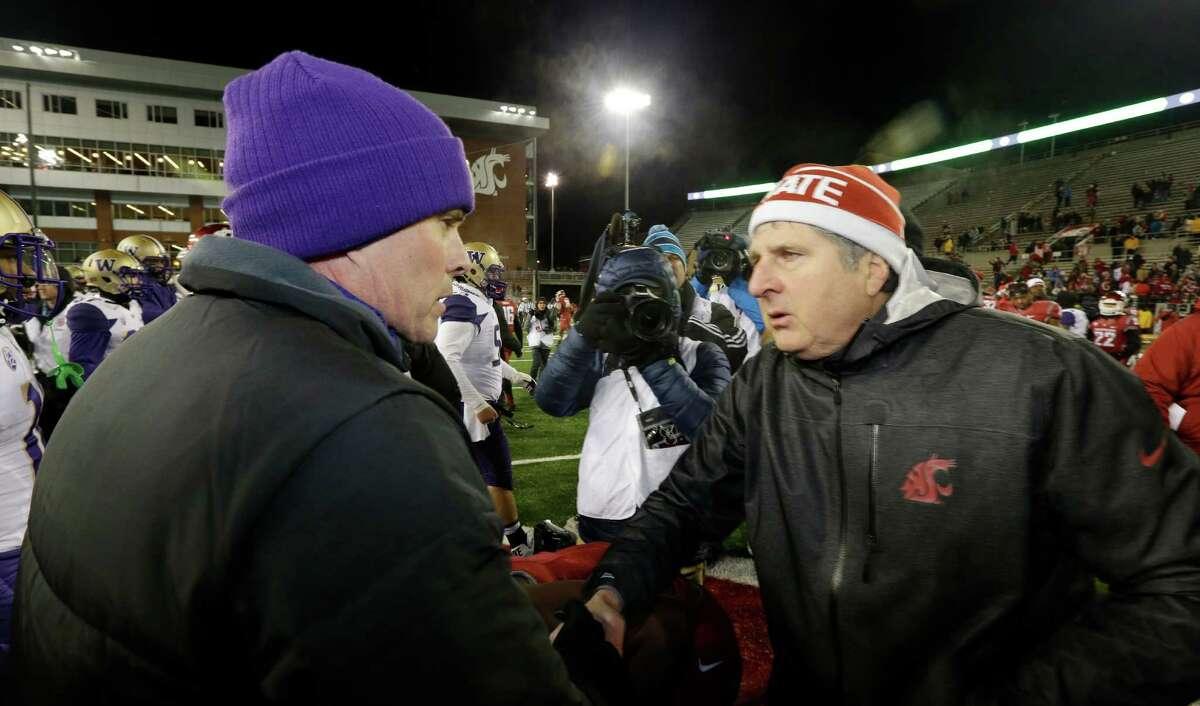 Washington coach Chris Petersen, left, shakes hands with Washington State coach Mike Leach after an NCAA college football game, Saturday, Nov. 29, 2014, in Pullman, Wash. Washington won 31-13. (AP Photo/Ted S. Warren)