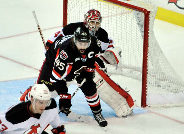 Zack Stortini, left, of the Binghamton Senators screens goalie, Yann Danis of the Albany Devils during their game at the Times Union Center on Sunday, Oct. 25, 2015, in Albany, N.Y.  (Paul Buckowski / Times Union)