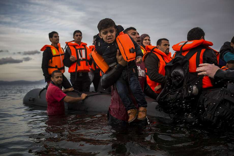 Volunteers assist refugees from a dinghy after they crossed a part of the Aegean sea from Turkey to the northeastern Greek island of Lesbos in November. Photo: Santi Palacios, Associated Press