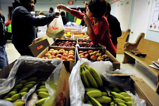 Volunteers bag up fruit for families at the Hope 7 Food Pantry on Tuesday, Nov. 24, 2015, in Troy, N.Y.  The pantry, which was started 46 years ago, has been giving out the Thanksgiving food baskets to the families they serve for over 15 years.  (Paul Buckowski / Times Union) Photo: PAUL BUCKOWSKI / 10034350A