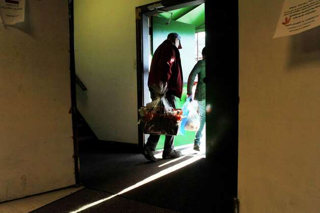Volunteer, Gary Nelson of Troy, helps a family carry out their food supplies at the Hope 7 Food Pantry on Tuesday, Nov. 24, 2015, in Troy, N.Y. (Paul Buckowski / Times Union) Photo: PAUL BUCKOWSKI / 10034350A