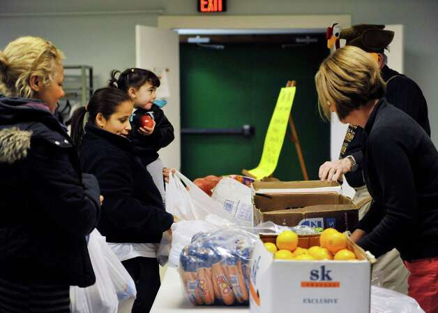 Zuleika Crespo of Troy and her daughter Bethany Rosario, 2, get fruit from volunteers at the Hope 7 Food Pantry on Tuesday, Nov. 24, 2015, in Troy, N.Y.   (Paul Buckowski / Times Union) Photo: PAUL BUCKOWSKI / 10034350A