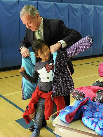 Albany Devils CEO Chris Ciceri helps ManRe Ka Paw, 7, try on a new coat during an event announcing over 1400 new coats, hats, gloves and scarves purchased with donations from the 2015 Cash for Coats program will help keep Albany kids warm this winter at Delaware Community School on Tuesday, Nov. 24, 2015 in Albany, N.Y. (Lori Van Buren / Times Union) Photo: Lori Van Buren / 10034386A