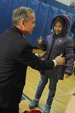 Albany Devils CEO Chris Ciceri gets the thumbs up from ManRe Ka Paw, 7, as she tries on a new coat during an event announcing over 1400 new coats, hats, gloves and scarves purchased with donations from the 2015 Cash for Coats program will help keep Albany kids warm this winter at Delaware Community School on Tuesday, Nov. 24, 2015 in Albany, N.Y. (Lori Van Buren / Times Union) Photo: Lori Van Buren / 10034386A