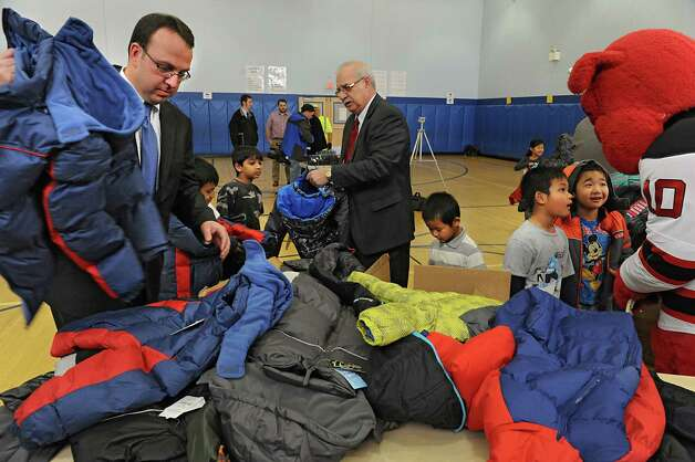 B. Lodge & Company former owner Jack Yonally, center, and his son Mark Yonally, left, help children pick out coats during an event  at Delaware Community School on Tuesday, Nov. 24, 2015 in Albany, N.Y. At the event it was announced that over 1400 new coats, hats, gloves and scarves purchased with donations from the 2015 Cash for Coats program will help keep Albany kids warm this winter. (Lori Van Buren / Times Union) Photo: Lori Van Buren / 10034386A