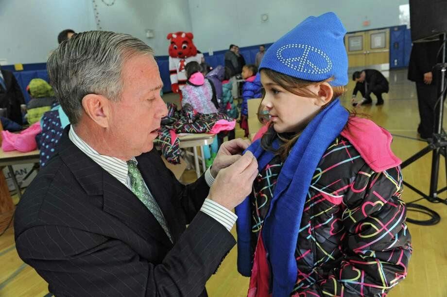 Albany Devils CEO Chris Ciceri helps Kaylee Kelly, 5, try on a new coat during an event announcing over 1400 new coats, hats, gloves and scarves purchased with donations from the 2015 Cash for Coats program will help keep Albany kids warm this winter at Delaware Community School on Tuesday, Nov. 24, 2015 in Albany, N.Y. (Lori Van Buren / Times Union) Photo: Lori Van Buren / 10034386A