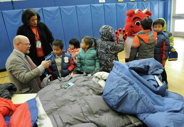 Delaware Community School Principal Kenneth Lein, left, and Albany School District Superintendent Dr. Marguerite Vanden Wyngaard help children pick out coats during an event  at Delaware Community School on Tuesday, Nov. 24, 2015 in Albany, N.Y. At the event it was announced that over 1400 new coats, hats, gloves and scarves purchased with donations from the 2015 Cash for Coats program will help keep Albany kids warm this winter. (Lori Van Buren / Times Union) Photo: Lori Van Buren / 10034386A