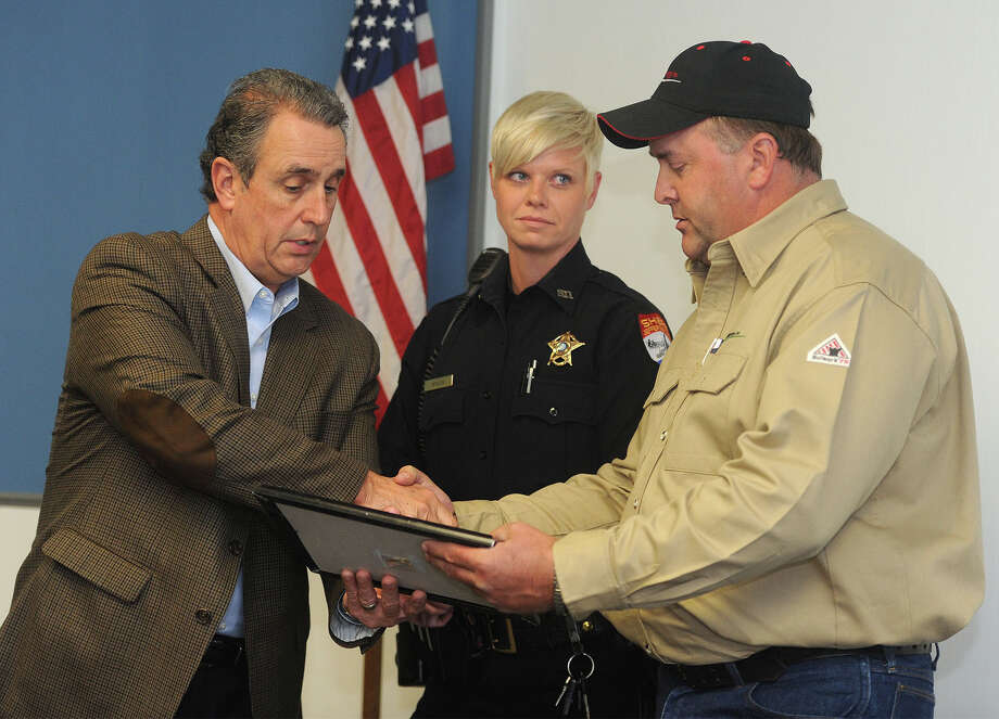 Jefferson County Sheriff Mitch Woods hands a Life Saving Award to Cody Sears during a ceremony on Monday. Sears and Deputy Alisha Steltz, centered, were awarded for aiding an unconscious driver whose car was on fire during an October traffic accident.  Photo taken Monday, November 23, 2015  Guiseppe Barranco/The Enterprise Photo: Guiseppe Barranco, Photo Editor
