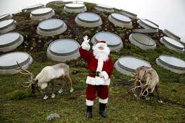 Santa Claus waves while flanked by reindeer Frosty (left) and Holiday on the roof of the California Academy of Sciences in San Francisco, California, on Tuesday, Nov. 24, 2015.