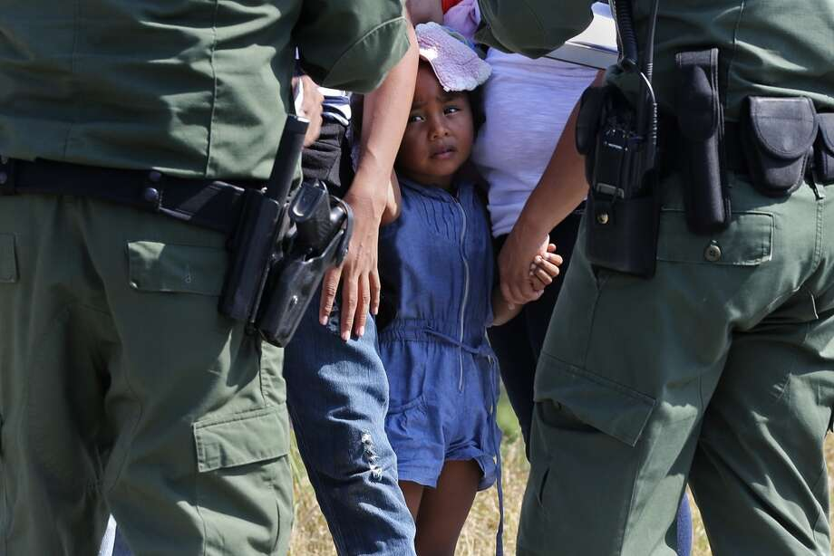 A young girl with U.S. Border Patrol agents near Anzalduas Park, southwest of McAllen, in 2014.