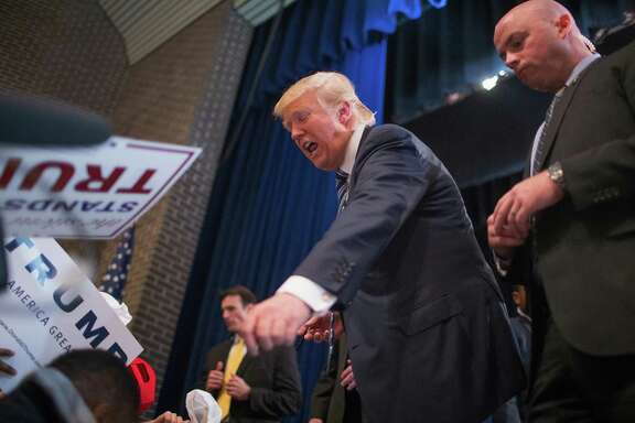 FORT DODGE, IA - NOVEMBER 12: Flanked by a member of his Secret Service detail Republican presidential candidate Donald Trump greets guests during a campaign stop at Iowa Central Community College on November 12, 2015 in Fort Dodge, Iowa. Yesterday Trump was assigned the protection detail. The stop comes on the heals of Tuesday's eight-candidate Republican debate in Milwaukee where a national poll of viewers declared Trump the winner.  (Photo by Scott Olson/Getty Images)