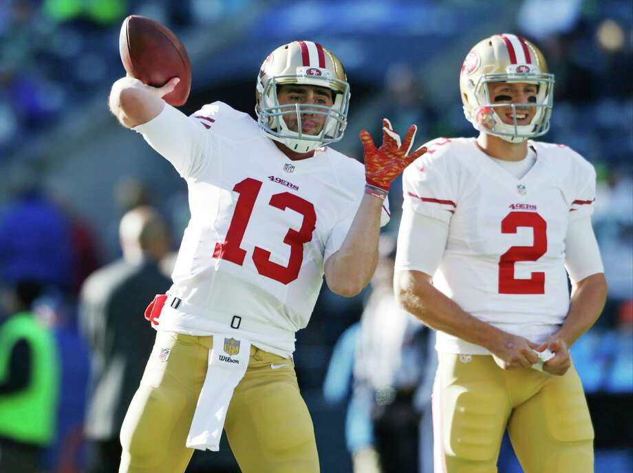Niners backup quarterback Dylan Thompson warms up Sunday in Seattle as starter Blaine Gabbert watches. Photo: John Froschauer / Associated Press / FR74207 AP