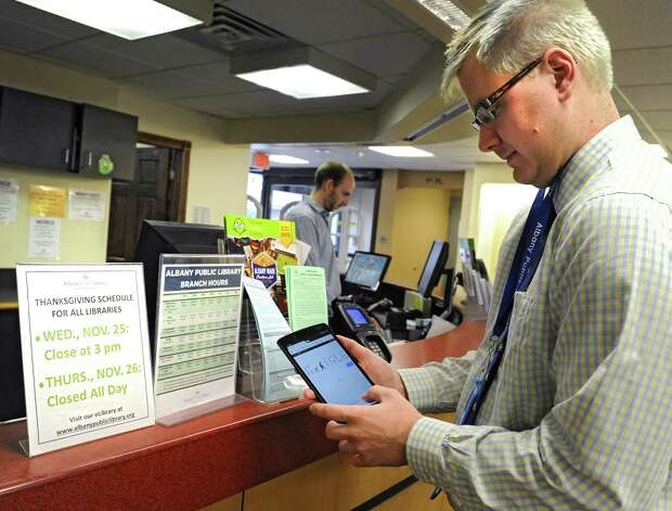 Library clerk Tim Furgal uses a borrowable tablet at the Albany Public Library on Tuesday, Nov. 24, 2015 in Albany, N.Y. The Samsung Galaxy Tab 2 tablets are part of a pilot program that began this week at the  Washington Avenue Branch. (Lori Van Buren / Times Union) Photo: Lori Van Buren / 10034427A
