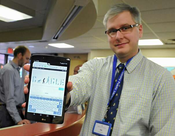 Library clerk Tim Furgal holds a borrowable tablet at the Albany Public Library on Tuesday, Nov. 24, 2015 in Albany, N.Y. The Samsung Galaxy Tab 2 tablets are part of a pilot program that began this week at the  Washington Avenue Branch. (Lori Van Buren / Times Union) Photo: Lori Van Buren / 10034427A