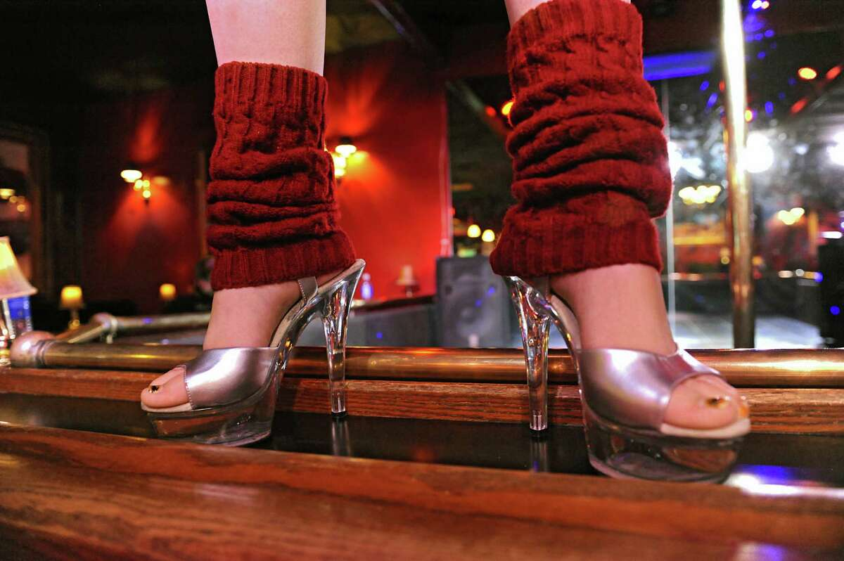 A dancer stands on the perimeter of a strip club stage. (Lori Van Buren / Times Union)