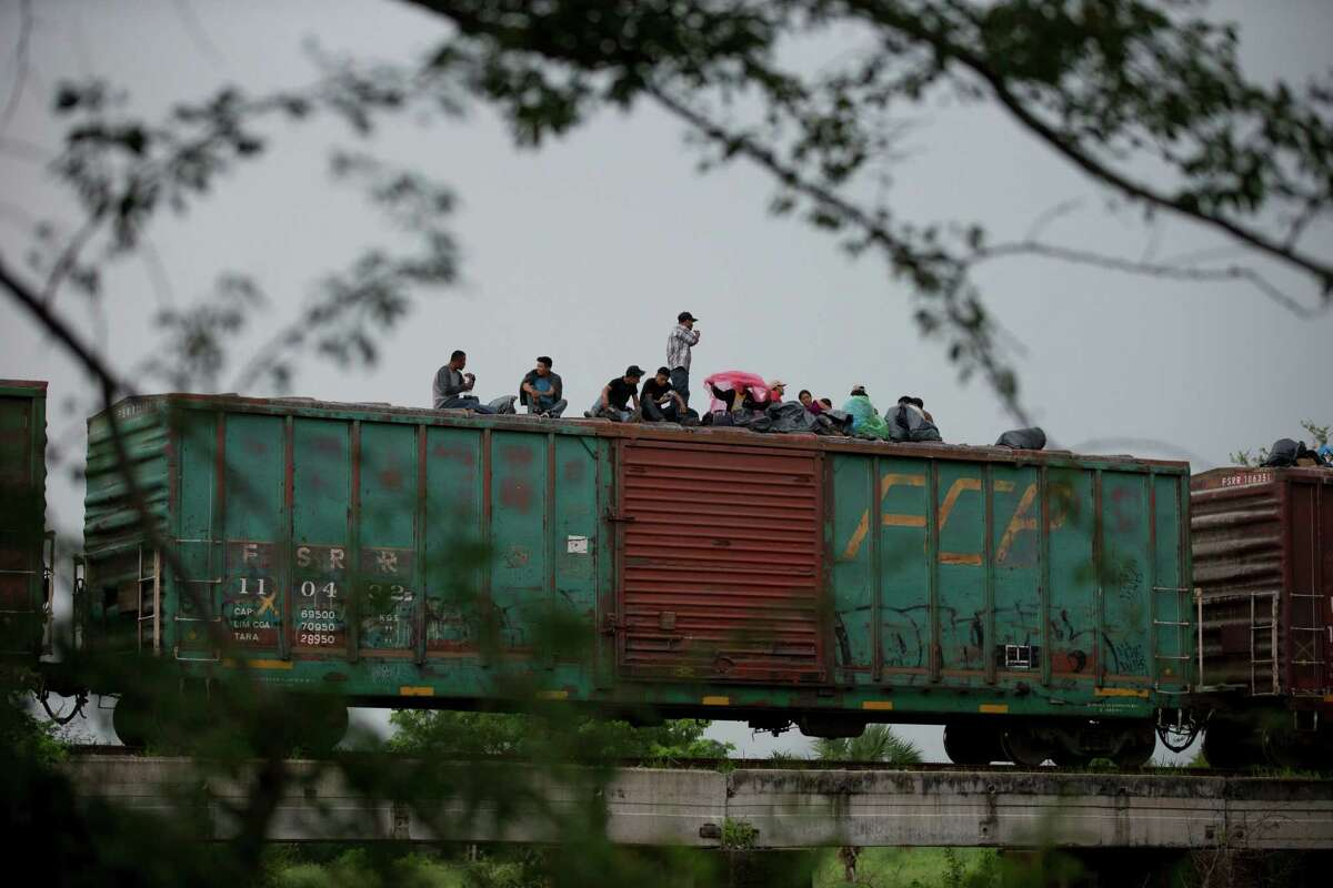 Central American migrants wait atop the freight train they had been traveling north on, as it starts to rain after the train suffered a minor derailment outside Reforma de Pineda, Chiapas state, Mexico in June 2014. .(AP Photo/Rebecca Blackwell, File)