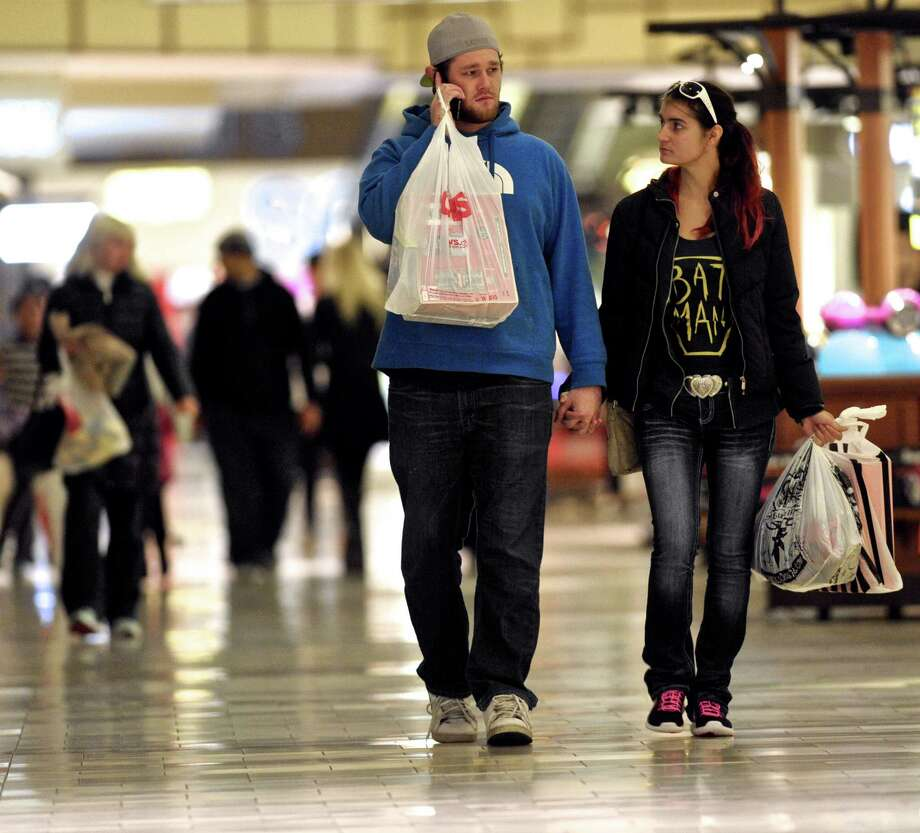 Casey Fredricks, of Bethel, and Dale McIntire, of Danbury, do a little holiday shopping at the Danbury Fair Mall on Tuesday night, November 24, 2015, in Danbury, Conn. Photo: H John Voorhees III, Hearst Connecticut Media / The News-Times