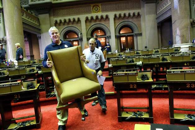 Assembly staffer Thomas O'Sullivan, left, helps carry in members' chairs, under the direction of shift supervisor Richard Bryant, right, after the carpet is cleaned in the Assembly Chamber on Tuesday, Nov. 24, 2015, at the Capitol in Albany, N.Y. Members tagged their chairs to ensure their proper return. (Cindy Schultz / Times Union) Photo: Cindy Schultz / 10034413A