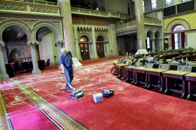 Steve Buell of Buell's Floor Covering in East Greenbush cleans the wool carpet in the Assembly Chamber on Tuesday, Nov. 24, 2015, at the Capitol in Albany, N.Y. Buell said he uses Host dry extraction carpet cleaner, which is comprised of ground corn cobs and a citrus-based solvent. It takes three workers three days to clean the nearly 10,000-square foot carpet.(Cindy Schultz / Times Union) Photo: Cindy Schultz / 10034413A