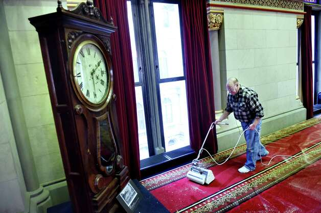 John Buell of Buell's Floor Covering in East Greenbush cleans the wool carpet in the Assembly Chamber on Tuesday, Nov. 24, 2015, at the Capitol in Albany, N.Y. The historic clock in the corner no longer works, but it is said to be the only thing that's right in the legislature twice a day. (Cindy Schultz / Times Union) Photo: Cindy Schultz / 10034413A