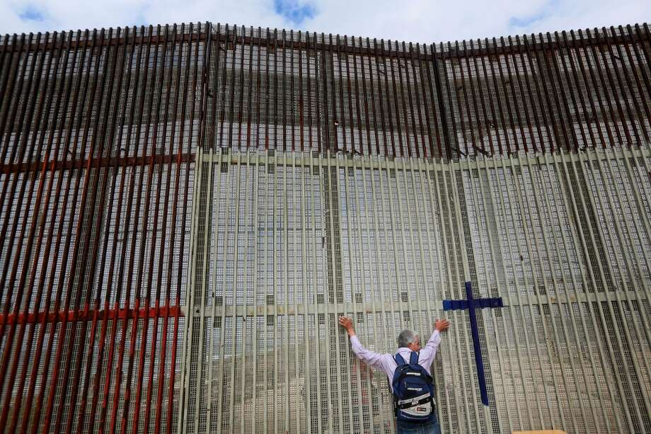 A man visits with Family members through the border fence along the U.S.-Mexico border on February 22, 2015 in Tijuana, Mexico.   Senior Republican senators said they expected Congress will avoid a shutdown over the Department of Homeland Security, which faces a partial shutdown on February 27 over a GOP push to roll back President Barack Obama's executive actions on immigration. Photo: Getty Images