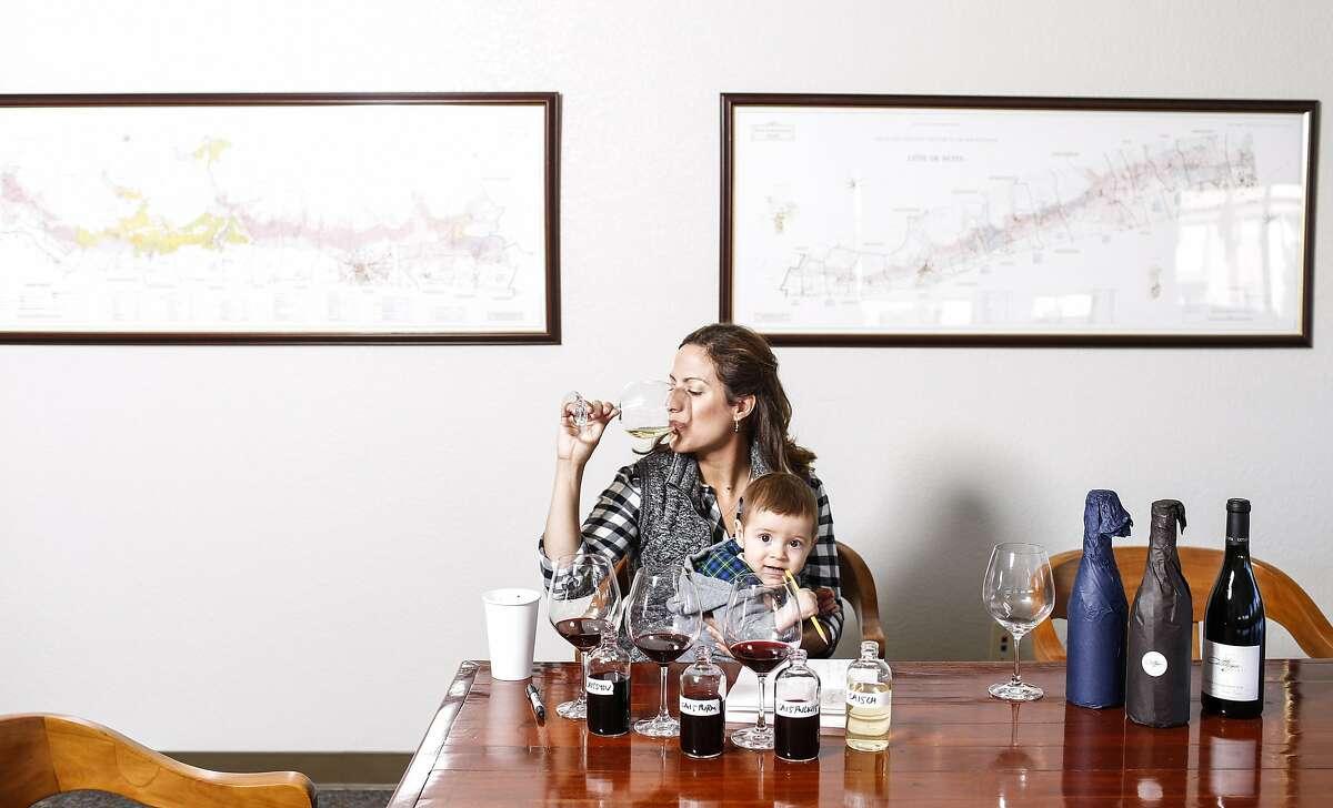 Bibiana Gonzalez-Rave of Cattleya wines tastes her Cattleya 2015 Chardonnay, Pratt Vineyard while holding her son, Lucas Richard Pisoni, on Tuesday, Nov. 24, 2015 in Santa Rosa, Calif.