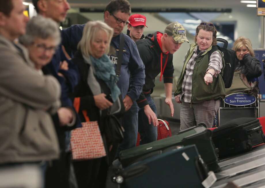 Barb Phillips (right) points out some luggage to her nephew Jake Klinger (second from right) as they collect their luggage with Phillips' son Ben Phillips (third from right in cap) at SFO after arriving to spend time with friends and family on Tuesday, November 24,  2015 in San Francisco, Calif. Photo: Lea Suzuki, The Chronicle