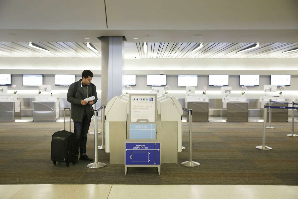 Brendan Klinkenberg uses a kiosk at the United Counter at SFO before departing on a flight to spend the holidays with family on Tuesday, November 24, 2015 in San Francisco, Calif.