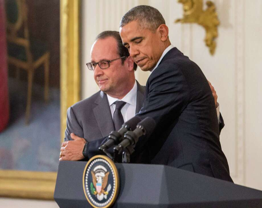President Barack Obama and French President Francois Hollande embrace during a joint news conference in the East Room of the White House in Washington, Tuesday, Nov. 24, 2015. Hollande's visit to Washington is part of a diplomatic offensive to get the international community to bolster the campaign against the Islamic State militants. (AP Photo/Andrew Harnik) ORG XMIT: DCAH114 Photo: Andrew Harnik / AP
