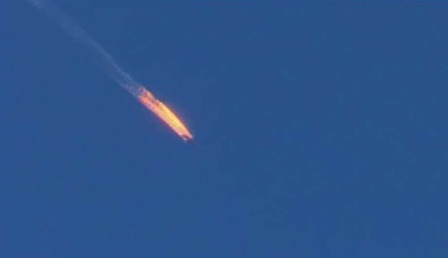 This frame grab from video by Haberturk TV, shows a Russian warplane on fire before crashing on a hill as seen from Hatay province, Turkey, Tuesday, Nov. 24, 2015. Turkey shot down the Russian warplane Tuesday, claiming it had violated Turkish airspace and ignored repeated warnings. Russia denied that the plane crossed the Syrian border into Turkish skies. (Haberturk TV via AP)  TURKEY OUT ORG XMIT: CAITH103 Photo: Uncredited / Haberturk TV