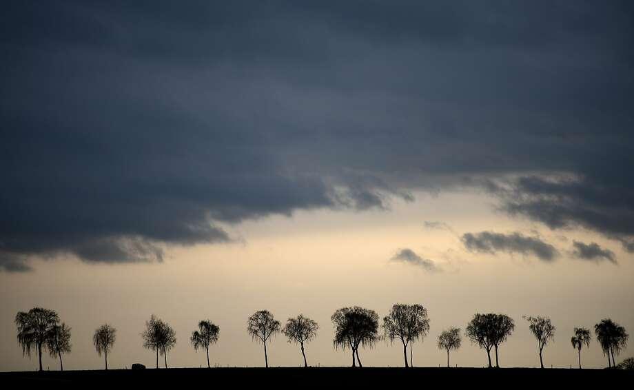 A car  drives along a street near Holzweiler , western Germany, while dark clouds  obscure the sky,  Tuesday Nov. 24, 2015. Photo: Jonas Guettler, Associated Press