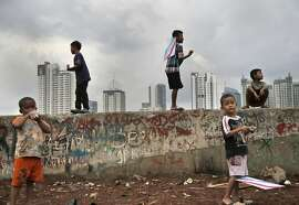 Children play as the skyline of the main business district is partially visible in the background, in Jakarta, Indonesia, Tuesday, Nov. 24, 2015. (AP Photo/Tatan Syuflana)