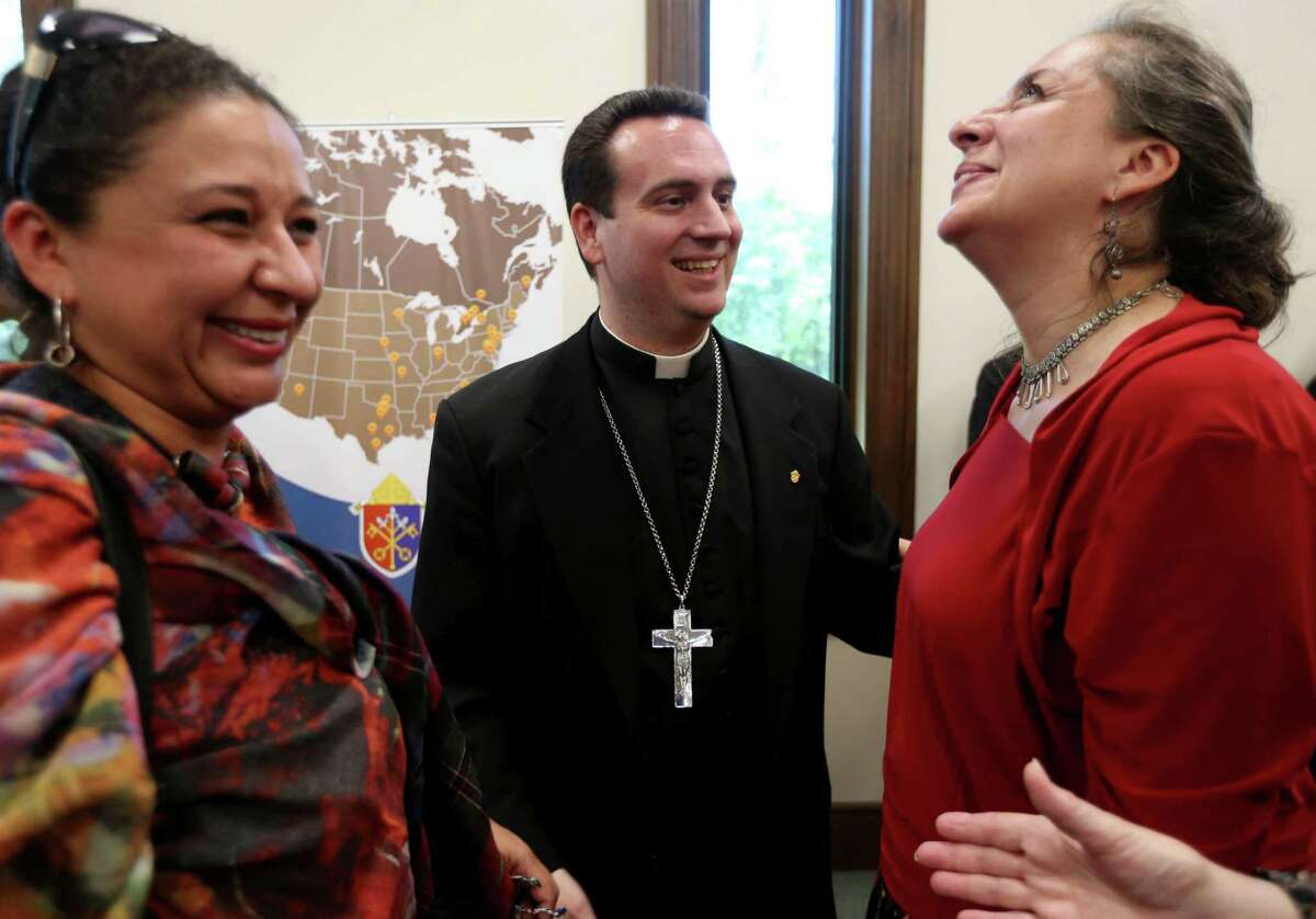 Bishop-elect Steven Lopes, center, celebrates with congregants Juliana Missas, left, and Catalina Brand on Tuesday. After spending years in Rome, Lopes said he is happy to be back in the U.S.
