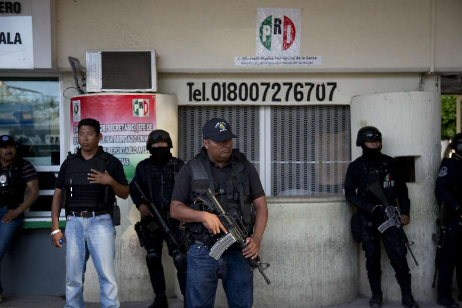 Police officers stand guard outside the municipality of Iguala, Mexico, the day federal officials disarmed local police and took over security after an attack on students that left at least six dead and 43 missing. Photo: Eduardo Verdugo, Associated Press