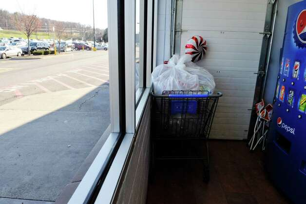 A shopping cart with a plastic bag filled with bottles appears to be discarded inside the bottle return area at the Walmart Supercenter off of Route 4 on Tuesday, Nov. 24, 2015, in Rensselaer, N.Y. (Paul Buckowski / Times Union) Photo: PAUL BUCKOWSKI / 10034422A