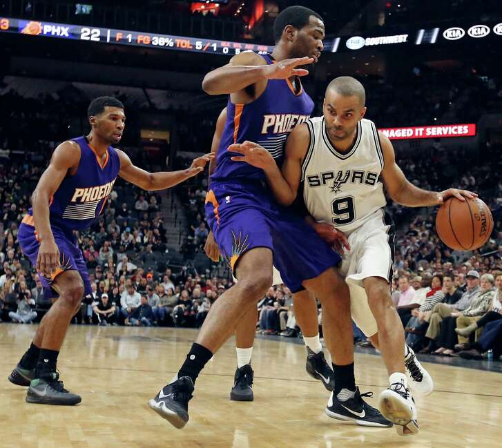 San Antonio Spurs' Tony Parker looks for room around Phoenix Suns' T.J. Warren as Ronnie Price moves in on the play during first half action Monday Nov. 23, 2015 at the AT&T Center.