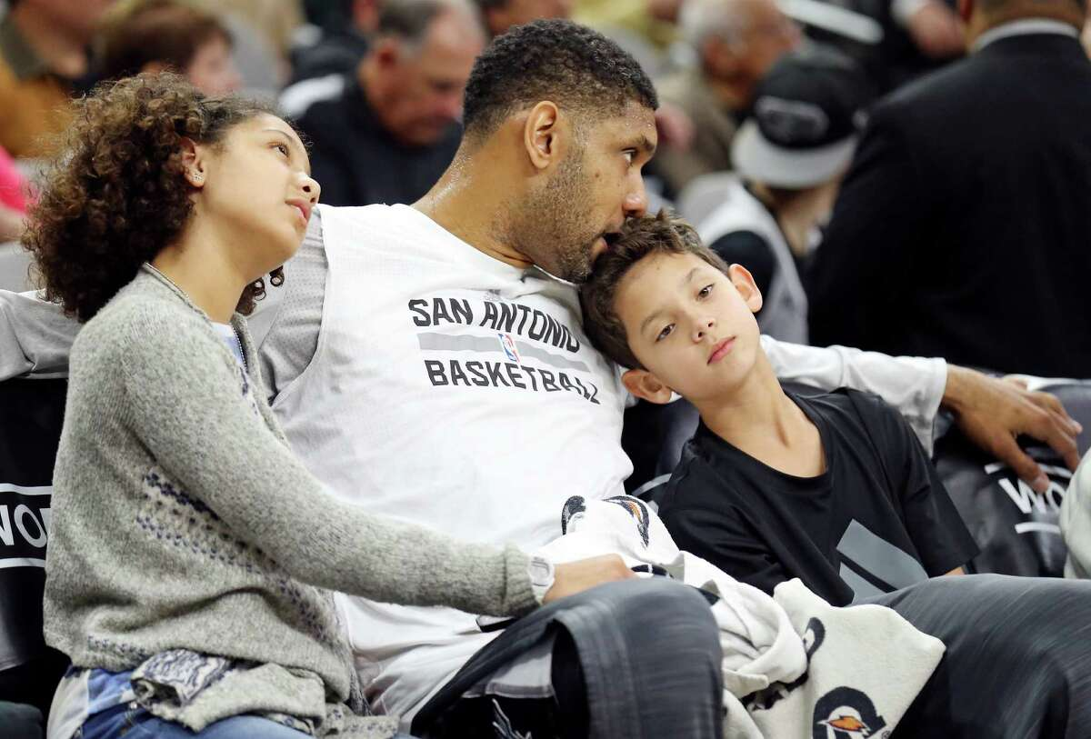 San Antonio Spurs' Tim Duncan sits with his children Sydney (left) and Draven before the game with the Phoenix Suns Monday Nov. 23, 2015 at the AT&T Center.