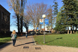 Students walk on the Western Washington University campus in Bellingham, Wash., after classes were canceled ,Tuesday, Nov. 24, 2015, because of threats over the weekend against minorities posted on YikYak, an anonymous social media platform populated by college students. (Perry Blankinship via AP)